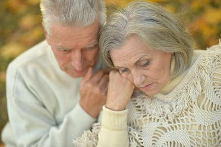 Portrait of sad enior couple in the park