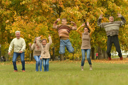 Happy smiling family relaxing in autumn park jumping