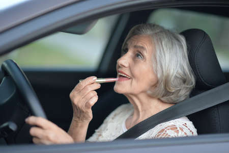 Portrait of senior woman putting lipstick in the car