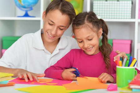 Cute brother and sister cutting colorful paper Foto de archivo