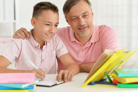 Father and son doing homework together at home 스톡 콘텐츠