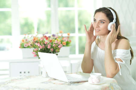 Young woman with laptop listening to music