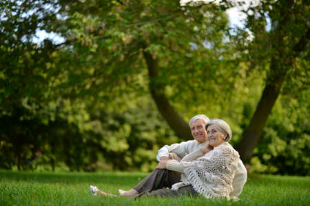 Portrait of happy senior couple sitting in park