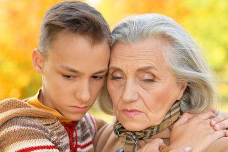 Close up portrait of grandmother and grandson hugging in park