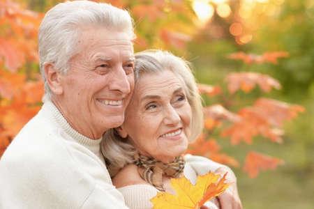Beautiful happy senior couple with autumn leaves