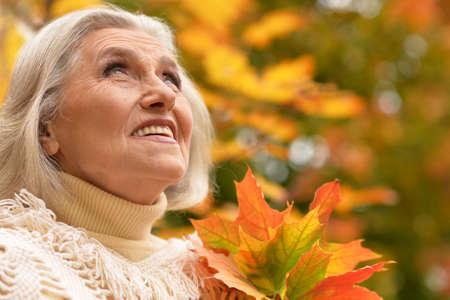 Happy senior beautiful woman in autumn park Standard-Bild