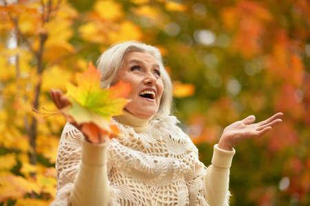 Happy senior beautiful woman in autumn park Zdjęcie Seryjne
