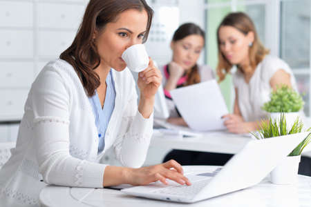 Young women sit at the table and work in a modern office
