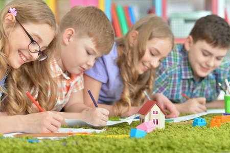 Children lying on floor drawing with pencils