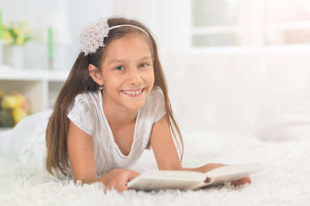 Little cute girl reading book at home
