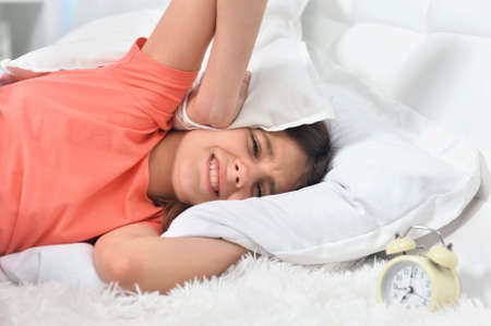 Cute little girl covering head trying to sleep in noisy room Stock Photo