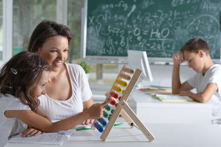 Woman teaching girl to use abacus indoors