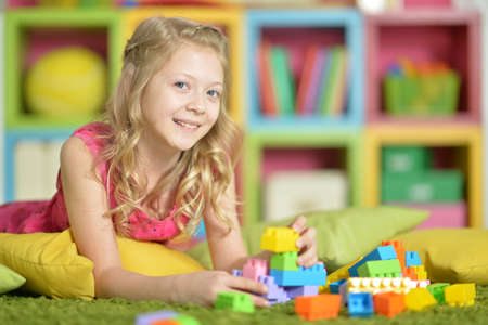 Little girl playing with colorful plastic blocks