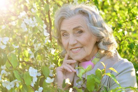 Portrait of beautiful senior woman posing near blooming tree