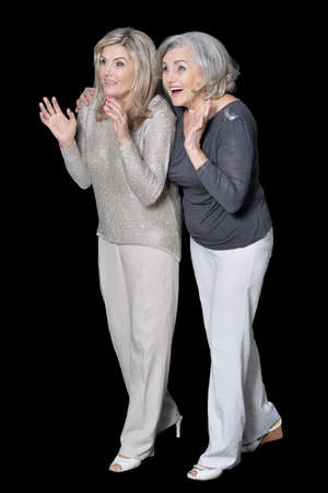Close up portrait of Two beautiful senior women posing against black background