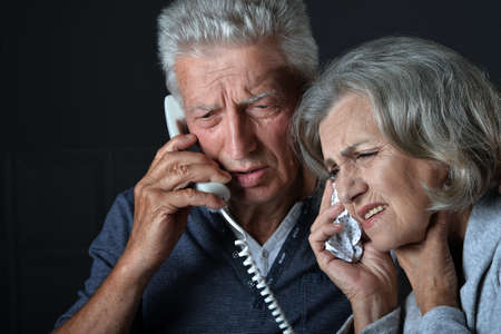 Portrait of sick elderly woman and man calling doctor