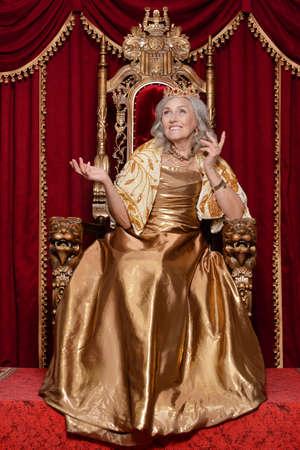 Portrait of beautiful senior queen on throne Foto de archivo