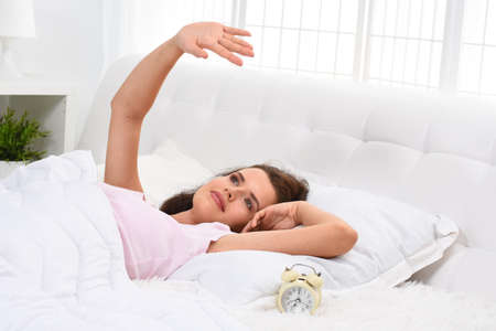 Beautiful young woman waking up on soft bed on morning Stock Photo