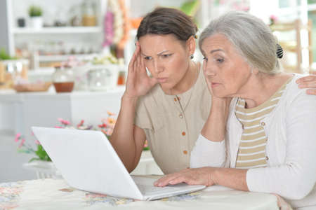 Mother and daughter sitting at table with laptop, at home