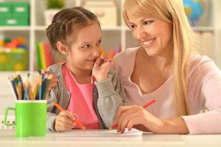 Cute girl with mother drawing at home Standard-Bild