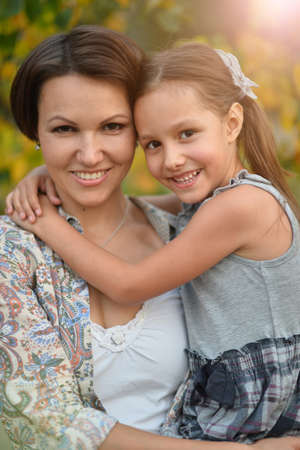 Portrait of happy mother and daughter smiling outdoors