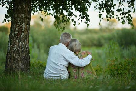 Back view of senior couple sitting on grass Foto de archivo
