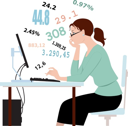 Young woman in glasses sitting in front of a computer, working with numbers