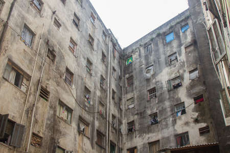 An abandoned building now occupied by social housing movement with white sky on the background. Internal view of the complex in C shape of this timeworn construction. San Paolo, Brazil, South America. Stock Photo