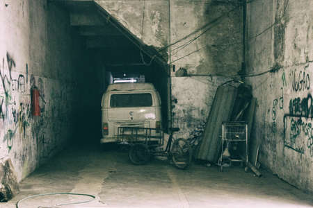 Old microbus, a carrying bike and a supermarket trolley parked in shabby garage with worn white vandalized walls. No people.