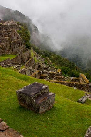 Vertical image of Machu Picchu stone ruins with low clouds on the nature on the background. Peru. South America. No people. 写真素材