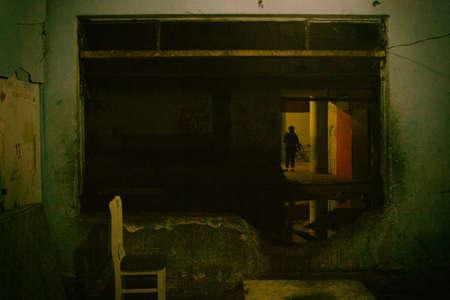Silla de madera blanca frente a un agujero en la pared destartalada utilizada como pasaje en un edificio en ruinas ocupado por un movimiento de vivienda social como hogar para los pobres. San Paolo. Brasil. Sudamerica.