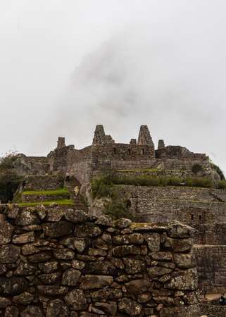 Vertical image of Machu Picchu stone ruins with low clouds on the nature on the background. Peru. South America. No people. Stock Photo