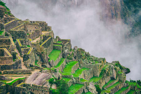 The secret and mysterious ruins of Machu Picchu covered in mist with the high Andes mountains on the background. The amazing prize of hiking the Inca Trail in Peru, South America. Stock fotó