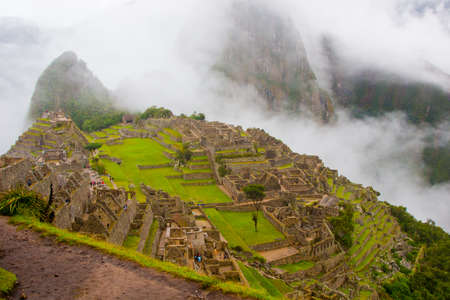 Classic view of the ancient mysterious city of Machu Picchu with intense clouds on the background in Peru. Astonishing wallpaper image.