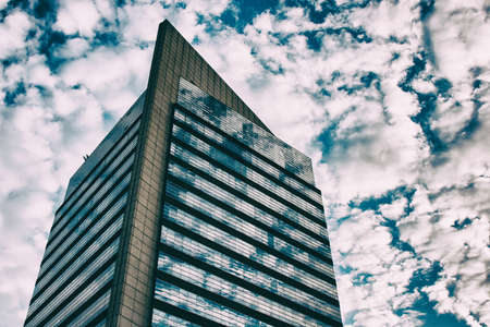 Beautiful cloudy sky reflected on modern glass windows office building Фото со стока