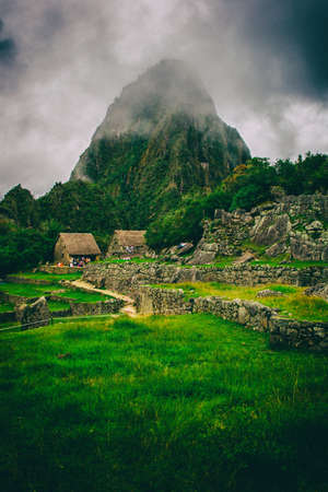 Vertical view of Machu Picchu stone ruins lost in the wild nature of the Andes mountains. Peru. South America. No people.