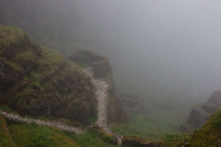 Historical ruins of the ancient Inca civilization covered by fog at dawn along the paved path Inca Trail in the Andes mountains in Peru, South America. Inspiring mysterious images.