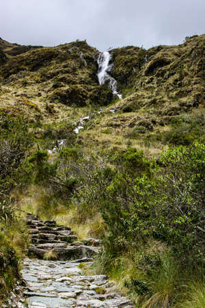 Surrounded by wild and ancient forest a waterfall on the stone paved path Inca Trail on the way to Machu Picchu, Peru.