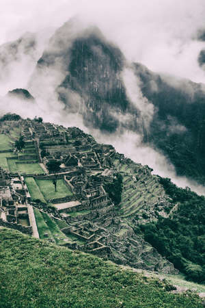 The secret and mysterious ruins of Machu Picchu covered in mist with the high Andes mountains on the background. The amazing prize of hiking the Inca Trail in Peru, South America. Stock Photo