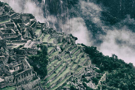 Beautiful background image of ancient stone ruins of Machu Picchu in the wild nature of the mountains with clouds. Peru. No people. Stock Photo