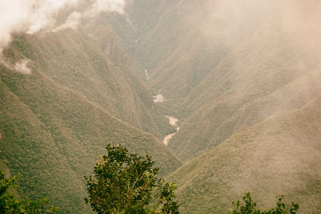 Serene red water river flow and a village on a valley in the Andes mountains in mist. Machu Picchu. Peru. No people. Stock Photo