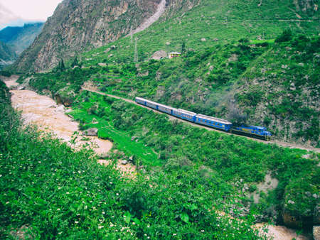 Train near a stormy red water river in the valley from the Inca Trail. Peru. No people.