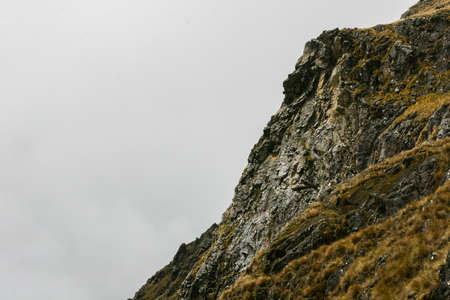 Detail of the side of a rocky mountain with green grass and intense clouds formation on the background. Cool wallpaper image. Peru. South America. No people. 写真素材