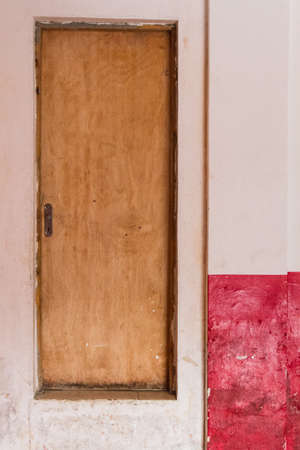 A wood door with a huge step with shabby white and red walls in a residential building. No people