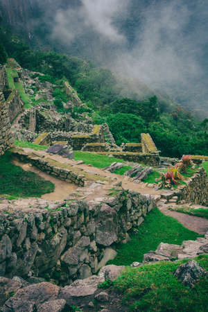 Vertical image of Machu Picchu stone ruins with low clouds on the nature on the background. Peru. South America. No people. 写真素材 - 104924737
