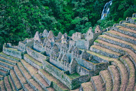 Inca Trail sightseen of an ancient stone ruin town with agriculture terraces with rich green wild forest and waterfall on the mountain on the background. Stock Photo