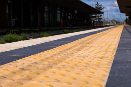 Low angle view of a safety yellow line on a train station with blue sky in the background. No people. Stock Photo