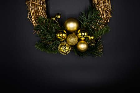 Wallpaper background texture of christmas wreath made of twig and golden balls and decorations with green branches isolated on black background. Stock Photo