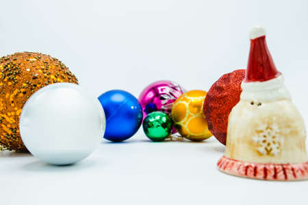 Colorful christmas baubles on white background with Santa figurine.