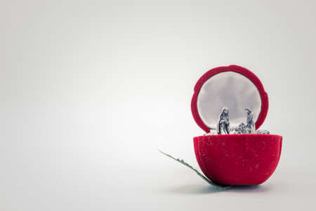 Christian nativity scene silver figures inside a red rose flower jewel velvet box isolated on white background.